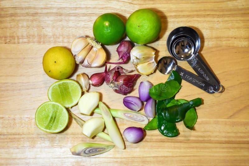 Lebensmittelinhaltsstoffkraut Kalk, Zitronengras, Knoblauch, Schalotten und Kaffirlindenblatt auf hölzernem Hintergrund stockfotos