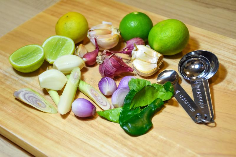 Lebensmittelinhaltsstoffkraut Kalk, Zitronengras, Knoblauch, Schalotten und Kaffirlindenblatt auf hölzernem Hintergrund lizenzfreies stockfoto