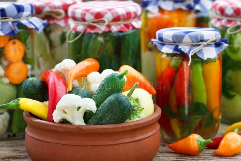 Lebensmittelkonserven in den Glasgefäßen und in der alten Schüssel stockbild