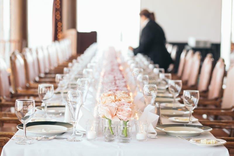 Lebensmittellieferant stellt Tabelle ein Lange Reihe von rosa Blumen lizenzfreie stockfotos