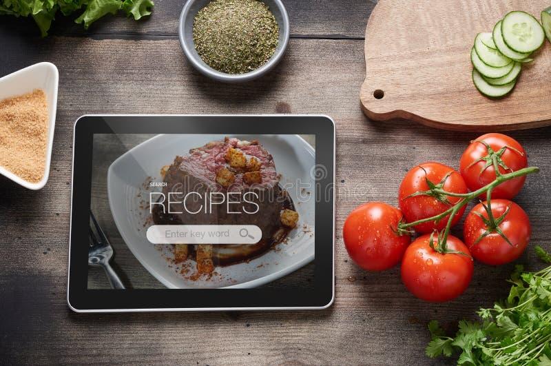 Lebensmittelrezepte auf Tablet-Computer stockbild
