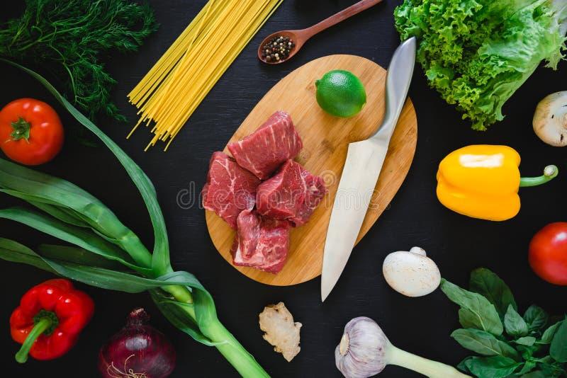 Lebensmittelzusammensetzung mit Fleisch auf hölzernem Brett, Messer, Teigwaren und Gemüse auf dunkler Tabelle Beschneidungspfad e stockfoto