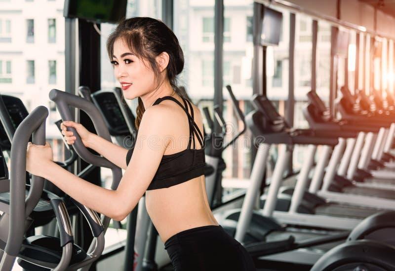 Lebensstil der jungen Frau unter Verwendung der Ausrüstungsmaschine elliptisch für tra stockbilder