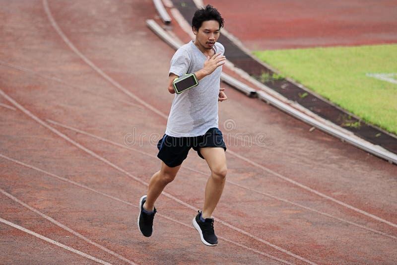 Lebensstil des jungen gesunden asiatischen Mannläufers, der auf Rennbahn läuft stockfotos