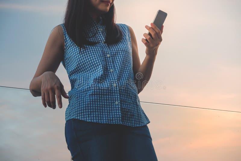 Lebensstil des modernen Leute-Konzeptes Junge Frau entspannend durch Ablesendaten oder Mitteilung über Smartphone An der Plattfor lizenzfreie stockfotos