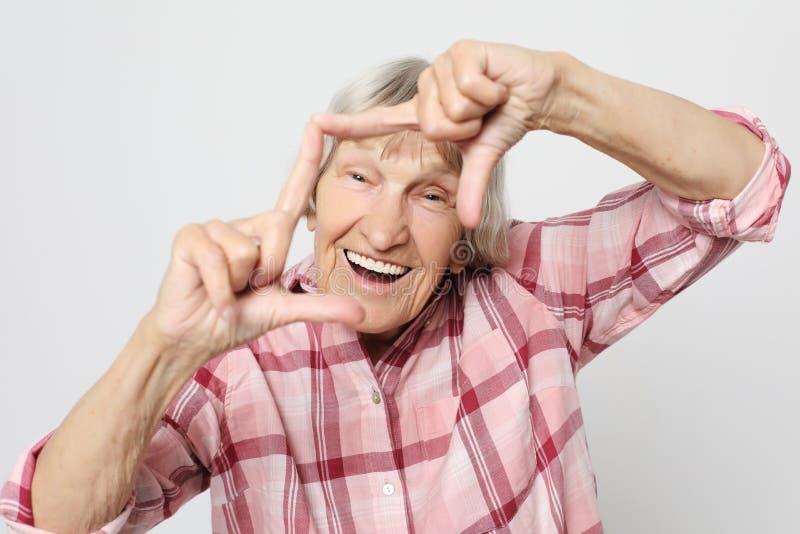 Lebensstil, Gefühl und Leutekonzept: Gealterte Großmutter mit entsetztem Gesicht Porträt der Großmutter mit rosa Hemd lizenzfreie stockbilder