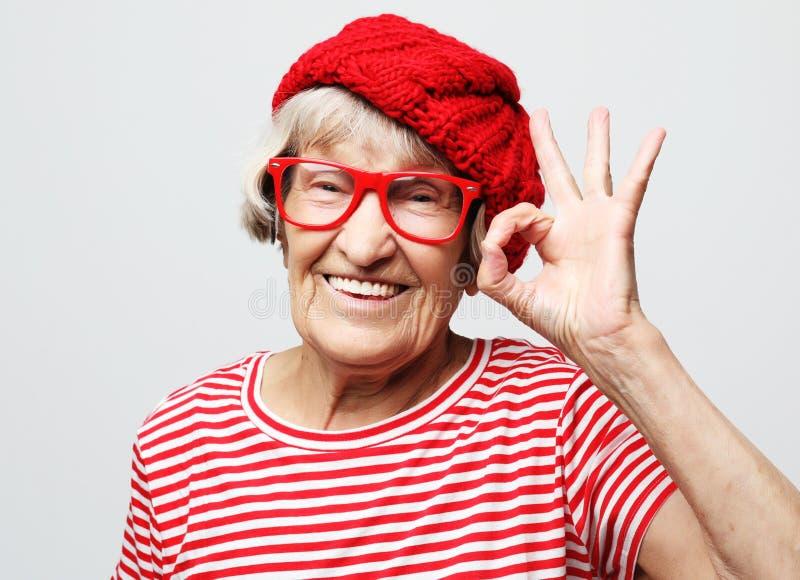 Lebensstil, Gefühl und Leutekonzept: Älteres glückliches Frauenvertretungs-O.K. lizenzfreie stockfotografie