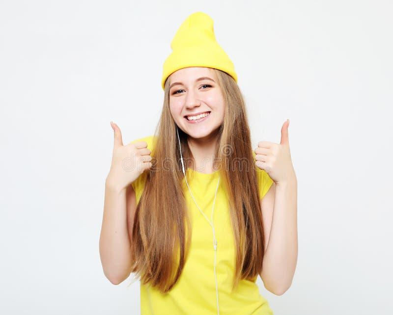 Lebensstil, Gefühl und Leutekonzept: Glückliche Frau, welche die gelbe Kleidung aufgibt Daumen trägt lizenzfreies stockbild