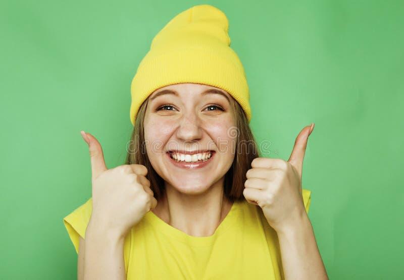 Lebensstil, Gefühl und Leutekonzept: Glückliche Frau, welche die gelbe Kleidung aufgibt Daumen trägt lizenzfreie stockfotos