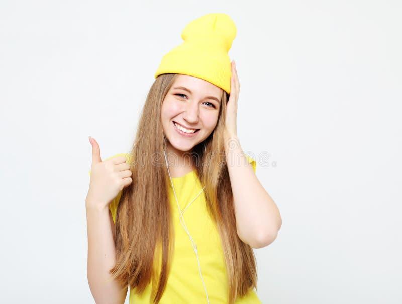 Lebensstil, Gefühl und Leutekonzept: Glückliche Frau, welche die gelbe Kleidung aufgibt Daumen trägt lizenzfreie stockbilder