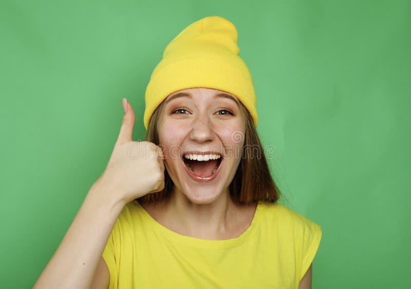 Lebensstil, Gefühl und Leutekonzept: Glückliche Frau, welche die gelbe Kleidung aufgibt Daumen trägt lizenzfreie stockfotografie