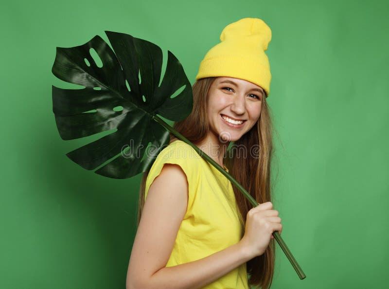 Lebensstil, Gefühl und Leutekonzept: Junge Schönheit, welche die gelbe zufällige Kleidung, Blatt von monstera halten trägt stockfotografie