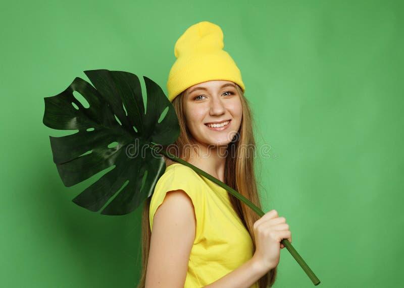 Lebensstil, Gefühl und Leutekonzept: Junge Schönheit, welche die gelbe zufällige Kleidung, Blatt von monstera halten trägt, lizenzfreie stockfotos
