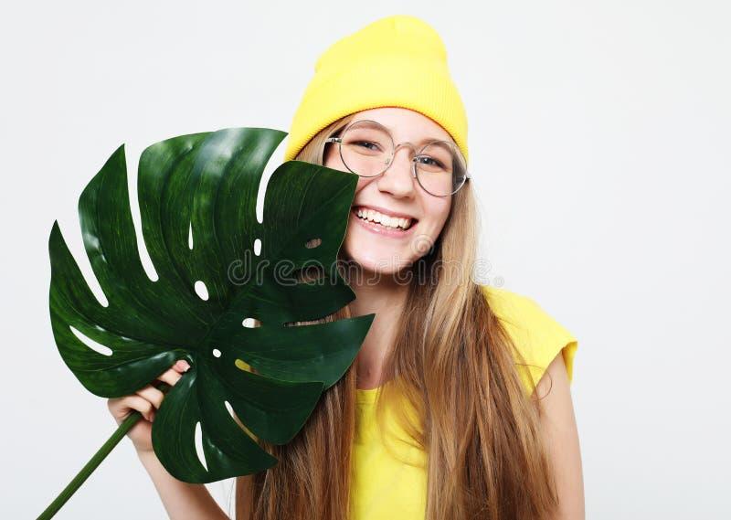 Lebensstil, Gefühl und Leutekonzept: Junge Schönheit, welche die gelbe zufällige Kleidung, Blatt von monstera halten trägt lizenzfreie stockfotos