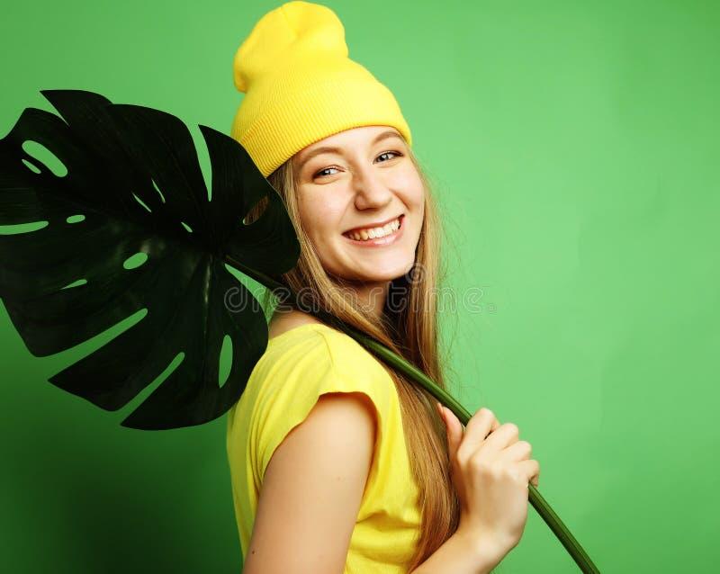 Lebensstil, Gefühl und Leutekonzept: Junge Schönheit, welche die gelbe zufällige Kleidung, Blatt von monstera halten trägt lizenzfreie stockfotografie