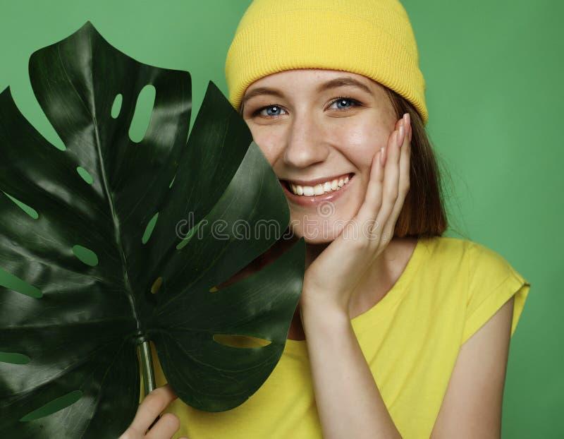 Lebensstil, Gefühl und Leutekonzept: Lächelnde Schönheit hinter großem Blatt stockfotos