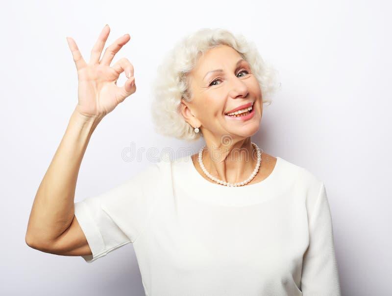 Lebensstil, Gef?hl und Leutekonzept: ?ltere gl?ckliche Frau, die einen Daumen aufgibt und die Kamera betrachtet lizenzfreie stockbilder