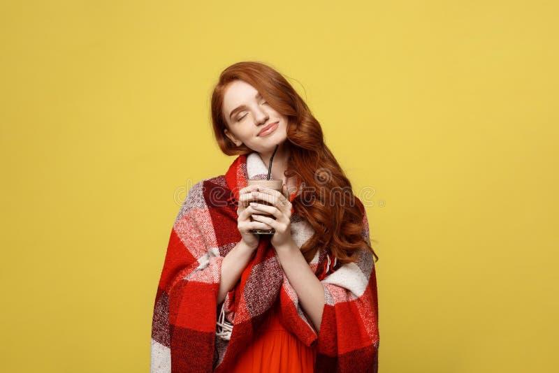 Lebensstil-Konzept: Das Porträt der Frau aalend mit Plaid und genießen die Trinkschokolade, die über klarem Gelb lokalisiert wird stockbild