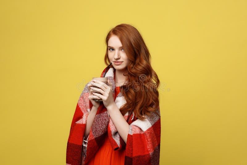 Lebensstil-Konzept: Das Porträt der Frau aalend mit Plaid und genießen die Trinkschokolade, die über klarem Gelb lokalisiert wird lizenzfreie stockfotografie