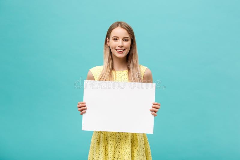 Lebensstil-Konzept: junges schönes Mädchen, das ein leeres Blatt Papier, gekleidet im Gelb, an lokalisiert lächelt und hält stockbilder
