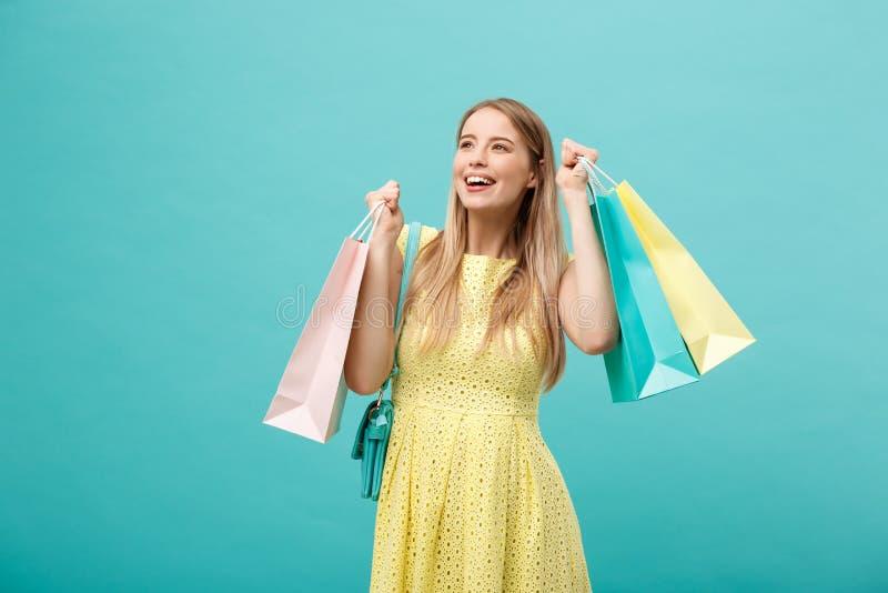 Lebensstil-Konzept: Porträt der entsetzten jungen attraktiven Frau im gelben Sommer, der mit Einkaufstaschen dressposing ist und stockfotografie