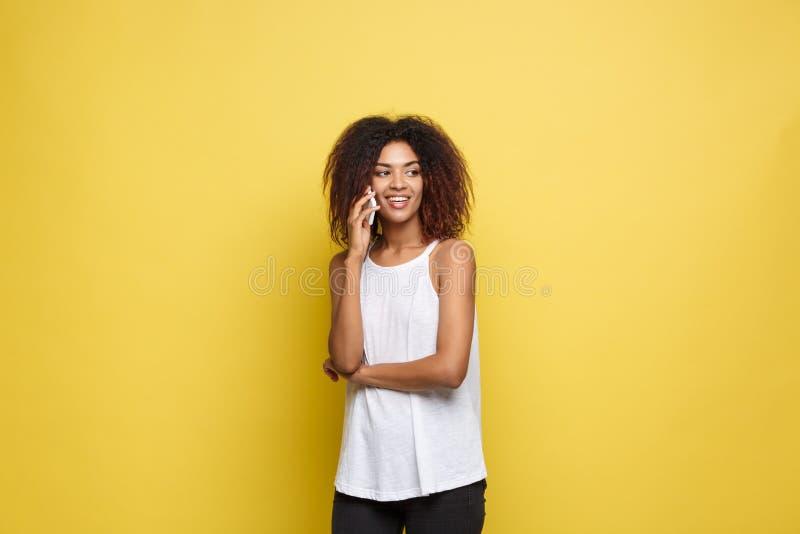 Lebensstil-Konzept - Porträt der frohen Unterhaltung der schönen Afroamerikanerfrau am Handy mit Freund gelb stockfoto
