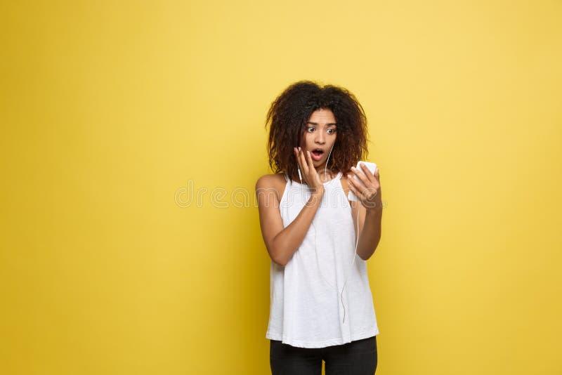 Lebensstil-Konzept - Porträt der schönen Afroamerikanerfrau, die mit etwas am Handy entsetzt Gelber Pastell stockbild