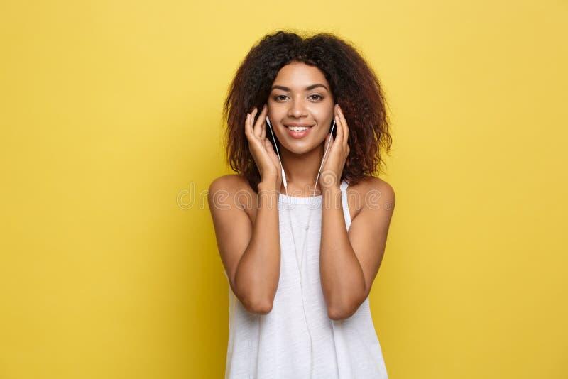 Lebensstil-Konzept - Porträt des frohen Hörens der schönen Afroamerikanerfrau Musik am Handy gelb lizenzfreie stockfotografie