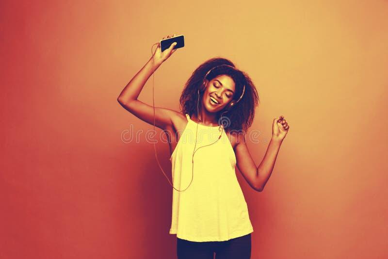 Lebensstil-Konzept - Porträt des frohen Hörens der schönen Afroamerikanerfrau Musik am Handy Kopieren Sie Platz lizenzfreie stockfotos