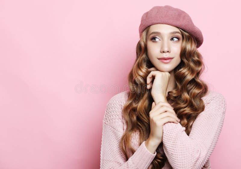 Lebensstil, Schönheit und Leutekonzept: Schönheitsmädchen mit der gelockten perfekten Frisur, die rosa Barett über weißem Hinterg lizenzfreies stockfoto