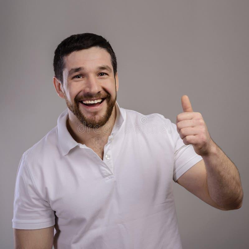 Lebensstil und Konzept der Menschen: Happy, gut aussehender Mann mit weißem T-Shirt, das Daumen über isolierten Hintergrund zeigt lizenzfreies stockbild