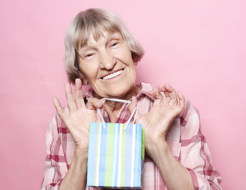 Lebensstil und Leutekonzept: Glückliche ältere Frau mit Einkaufstasche über rosa Hintergrund stockbilder