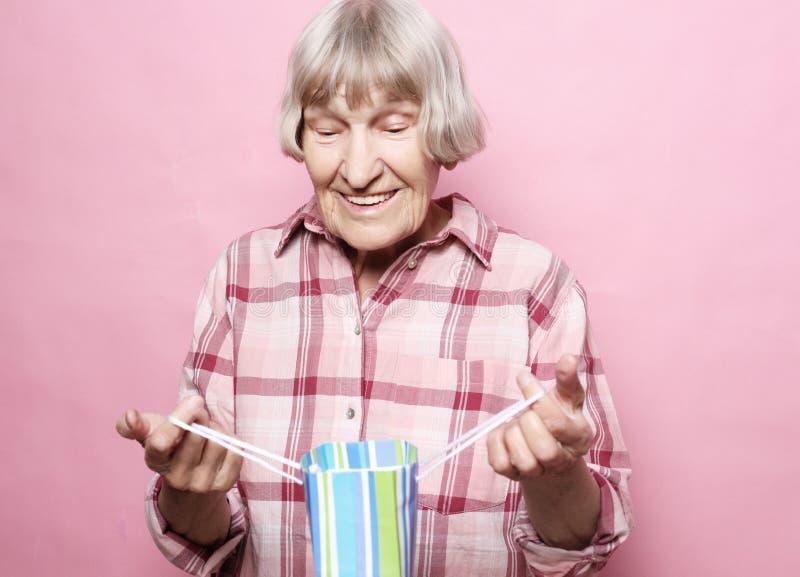 Lebensstil und Leutekonzept: Glückliche ältere Frau mit Einkaufstasche über rosa Hintergrund lizenzfreie stockbilder