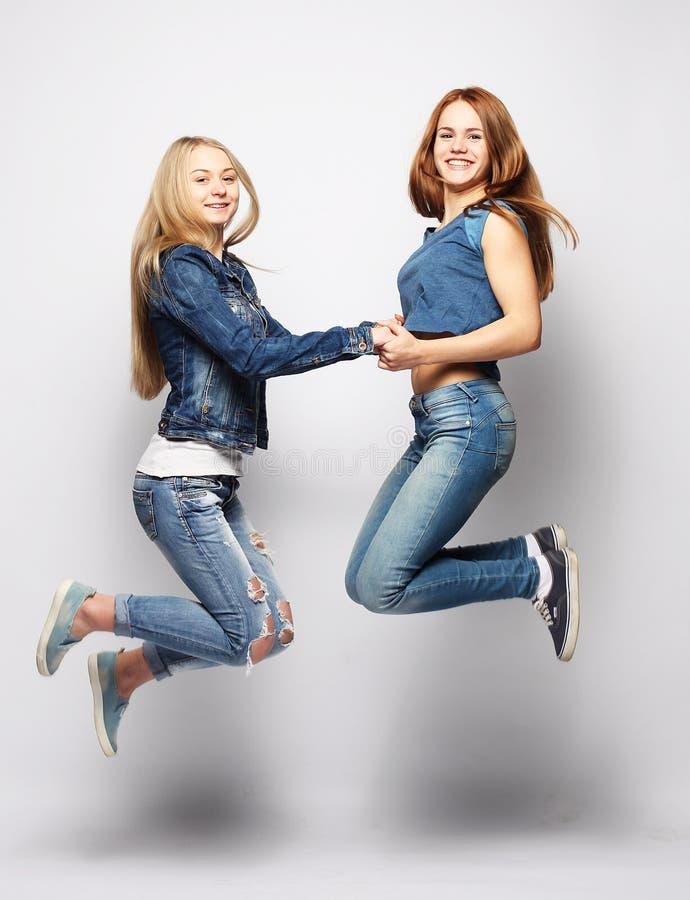 Lebensstil und Leutekonzept: Glückliche Mädchen, die über weißen bq springen lizenzfreie stockfotografie
