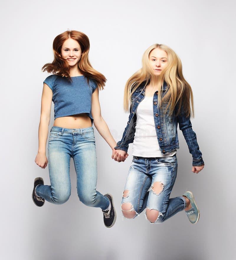 Lebensstil und Leutekonzept: Glückliche Mädchen, die über weißen bq springen stockfotografie