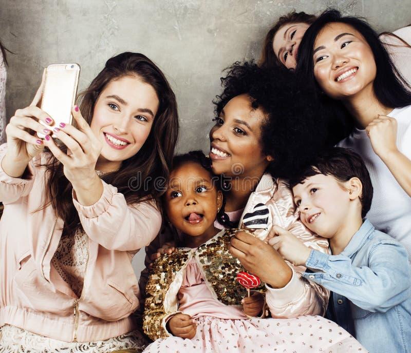 Lebensstil und Leutekonzept: junge hübsche Verschiedenartigkeitsnationsfrau mit den verschiedenen Alterskindern, die am Geburtsta lizenzfreie stockbilder