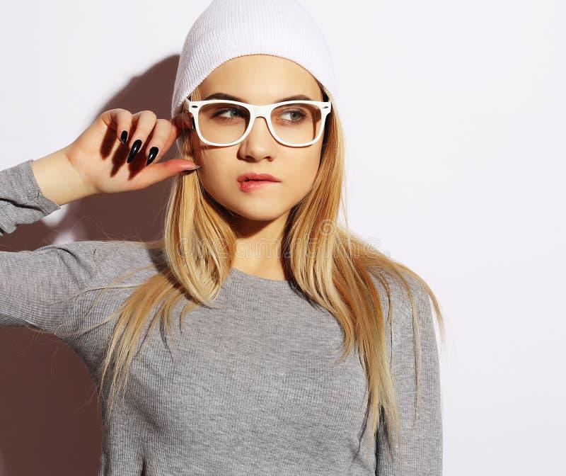 Lebensstil und Leutekonzept: Junge nette lächelnde tragende weiße Gläser und Hut des Hippie-Mädchens Gefühl auf Gesicht stockbild