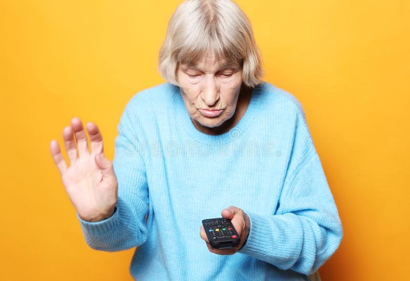 Lebensstil und Leutekonzept: lustige Großmutter hält ein Fernsehen entfernt über gelbem Hintergrund lizenzfreies stockfoto