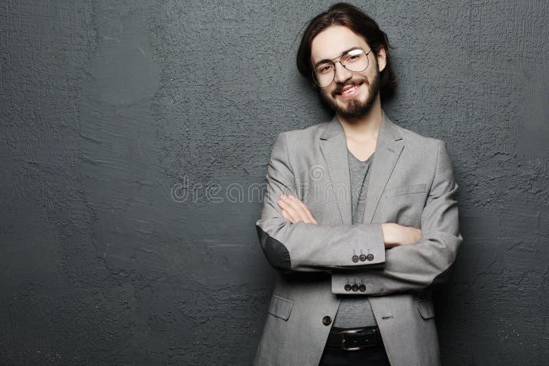 Lebensstil und Leutekonzept: Porträt des hübschen jungen Mannes mit Lächeln auf dunklem Hintergrund lizenzfreies stockbild
