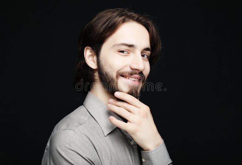Lebensstil und Leutekonzept: Porträt des hübschen jungen Mannes mit Lächeln auf dunklem Hintergrund stockbild