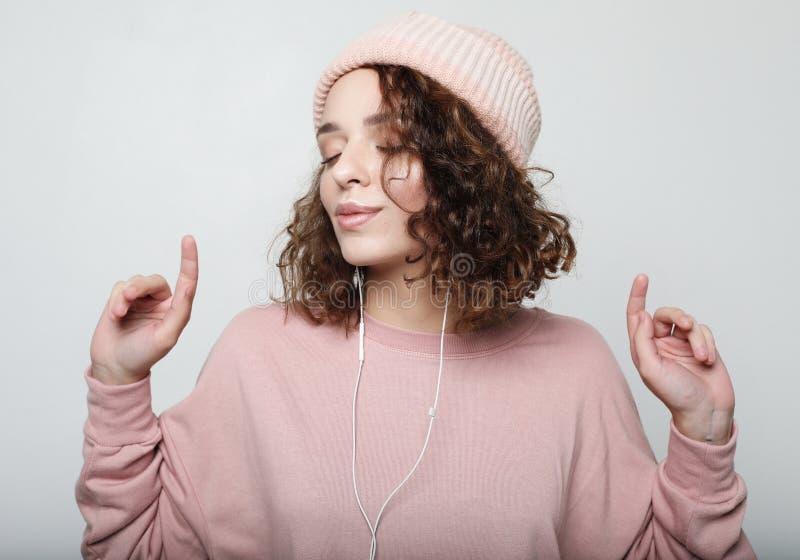 Lebensstil und Leutekonzept: Schöne junge Frau im Kopfhörer stockfotografie
