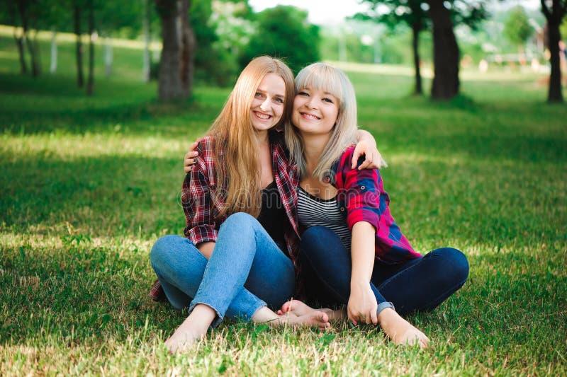 Lebensstil und Leutekonzept: Zwei junge Freundinnen, die zusammen sitzen und Spaß haben stockfotografie