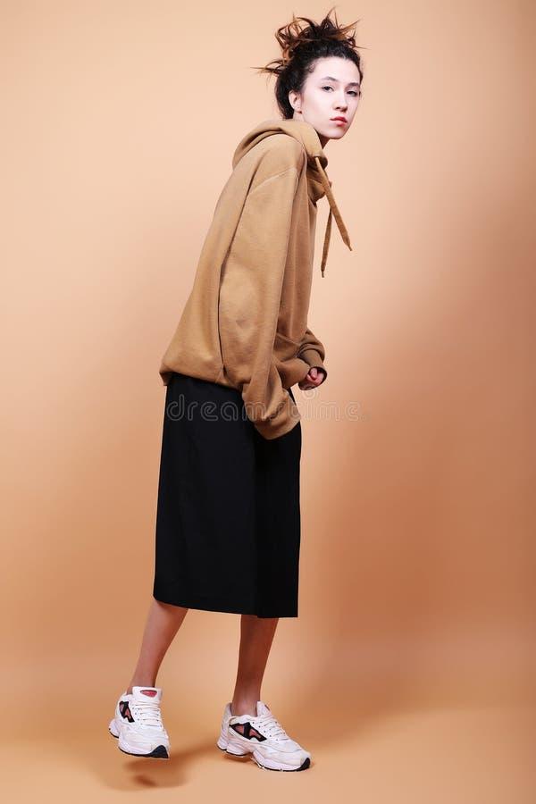 Lebensstil und Modekonzept: schöne Brunettefrau, welche die zufällige Kleidung, werfend auf beige Hintergrund trägt auf lizenzfreies stockfoto