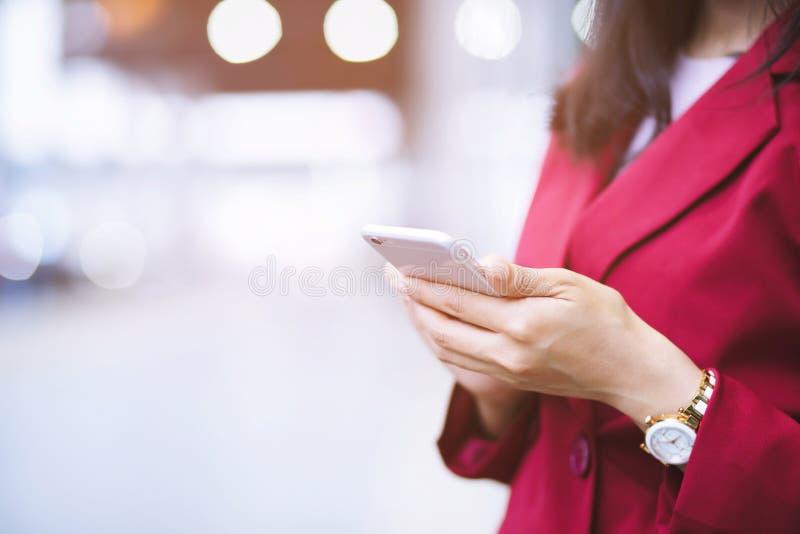 Lebensstilabschluß herauf Handgeschäftsfrauen in den Klagen färben das Rot, das aufpassende Mitteilung am intelligenten Mobiltele stockfotos