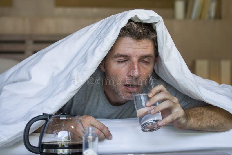 Lebensstilausgangsporträt des jungen erschöpften und vergeudeten Mannes, der leidende Kopfschmerzen und Kater, nachdem Alkohol an stockbilder