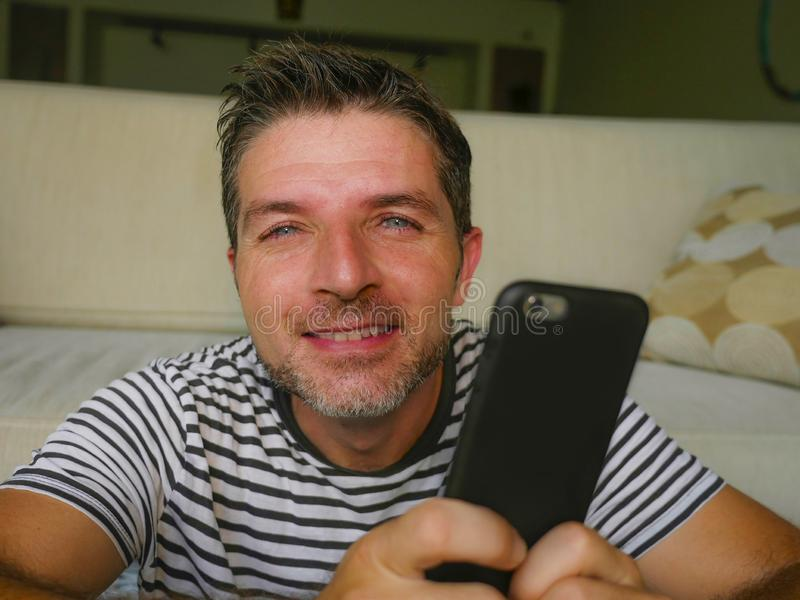 Lebensstilausgangsporträt des jungen glücklichen und attraktiven Mannes 30s unter Verwendung Internet-Datierung App oder des Mitt lizenzfreie stockbilder