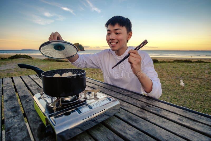 Lebensstilbild des jungen glücklichen asiatischen Fleisch fressenden heißen Topfofens auf einer Tabelle im Freien entlang Strand  lizenzfreies stockfoto