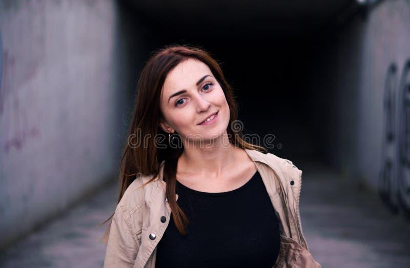 Lebensstilbild eines behaarten kaukasischen Mädchens der jungen hübschen Kastanie, das aus dem dunklen konkreten Korridorlächeln  lizenzfreie stockbilder