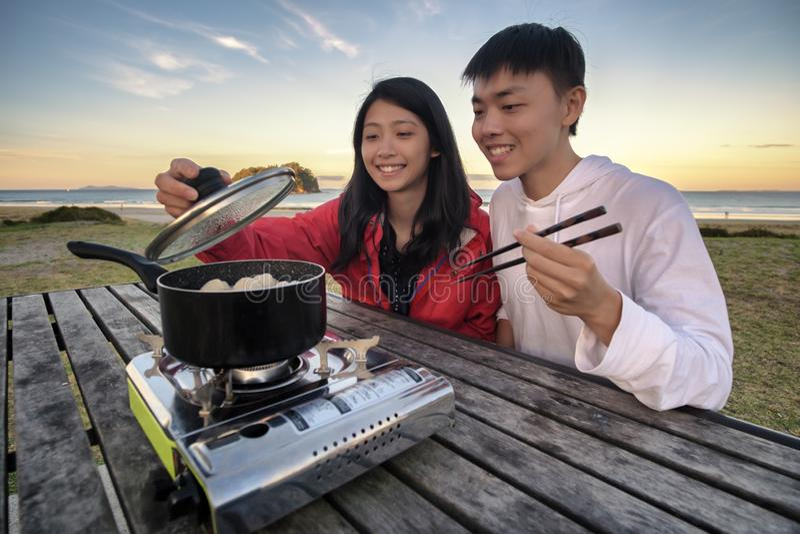 Lebensstilbild von den jungen glücklichen asiatischen Paaren, die heißen Topfofen auf einer Tabelle im Freien entlang Strand esse stockfoto