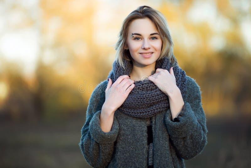 Lebensstilfoto im Freien von jungen schönen Blondinen Weinlesemantel des gemütlichen Schals des Fallherbstparks im grauen Filmfil lizenzfreies stockbild